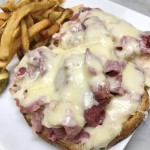 Roast beef reuben served with pickles and fries