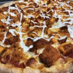 Pizza served with buffalo breaded chicken and ranch dressing